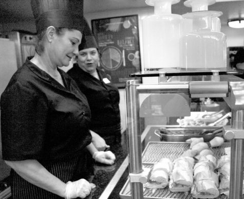 Yamila Cobos and Roherdy Garlobo enjoy a brief moment to chat after the lunchtime rush subsides. Both have been working in the RE dining hall for more than a decade.
