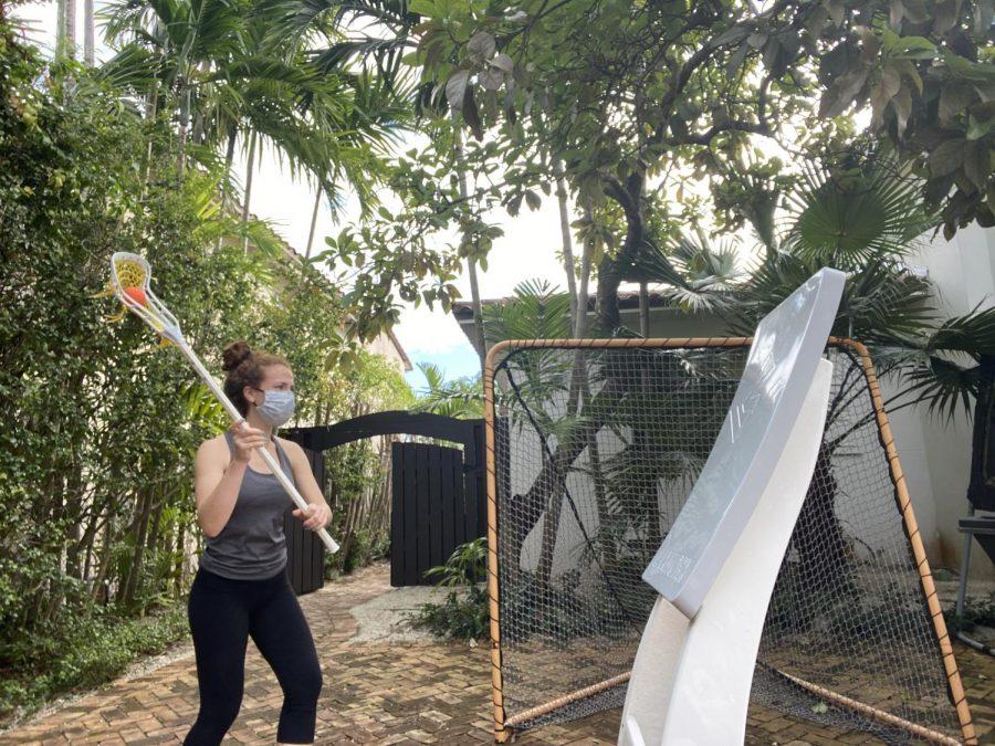 Rachel Bienstock '21, masked, practices lacrosse in her back yard.