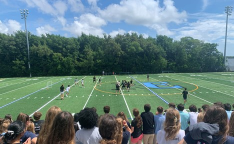Students watch the seniors (in black) play the freshmen on the field in the Freshmen Friday soccer game.