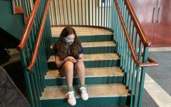 Cianna Vengoechea Schiff 25 sits on the steps of Lewis Auditorium looking solemnly at her phone.